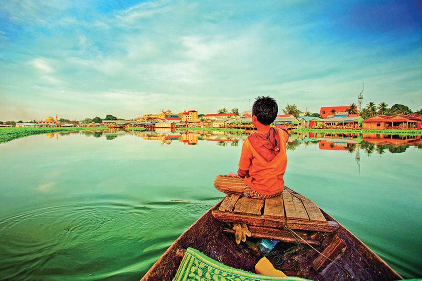 image Cambodge Garcon sur un petit bateau surplombant le lac  fo